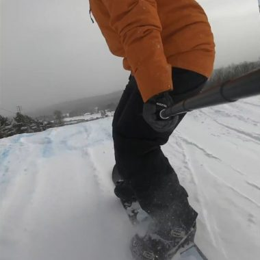 snowboarder orange jacket about to take off jump terrain park