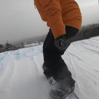 snowboarder orange jacket about to take off jump terrain park
